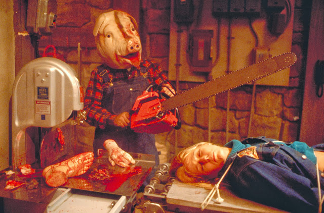 Vincent med motorsåg i hängselbrallor och grismask